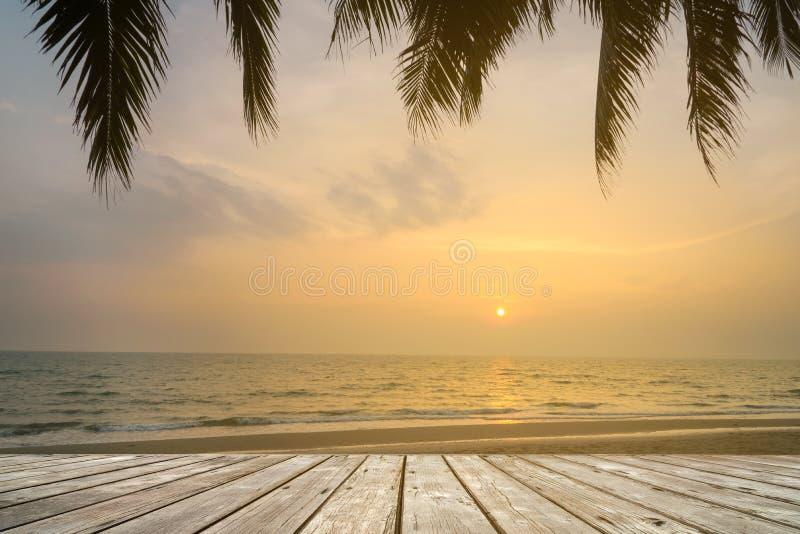 Träterrassen över den tropiska östranden med kokosnöten gömma i handflatan på solnedgång- eller soluppgångtid arkivfoto