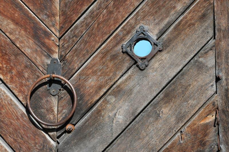 Trätextur av de gamla portarna med dörrknackaren och en visning fotografering för bildbyråer