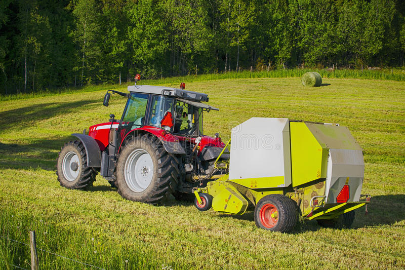 Trätor and hay-bale machinery in action. Farming traktor and hale-bale machinery, latest models stock photos