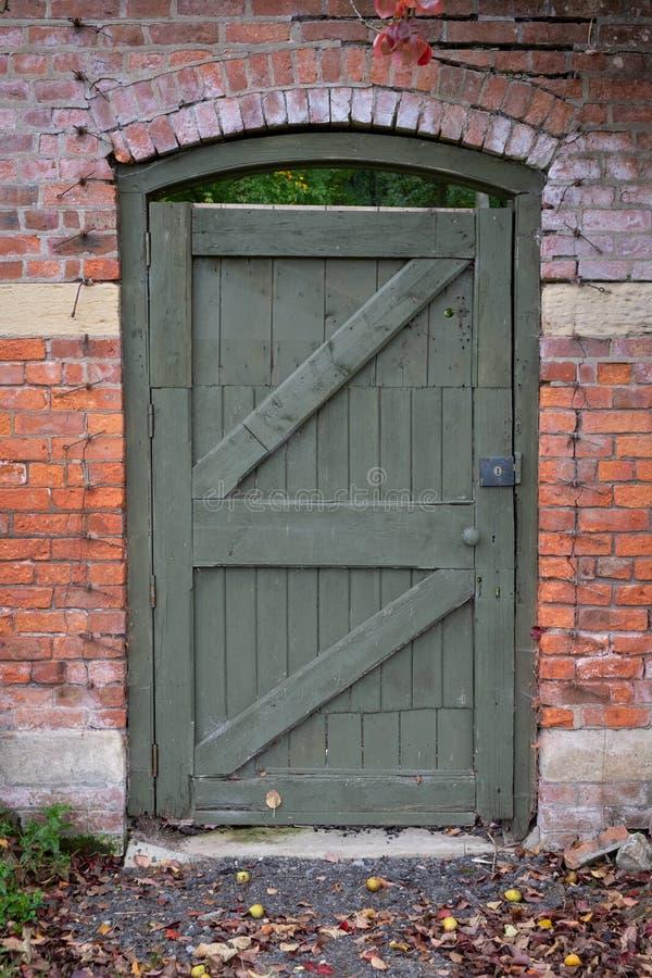 Träträdgårds- dörr i tegelstenvägg arkivfoton