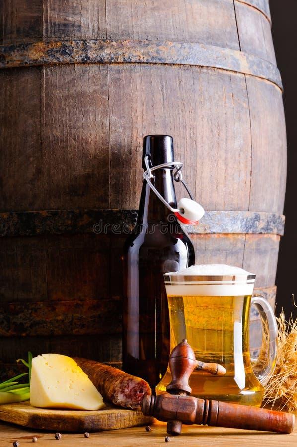 Trätrumma med öl och mat arkivfoton