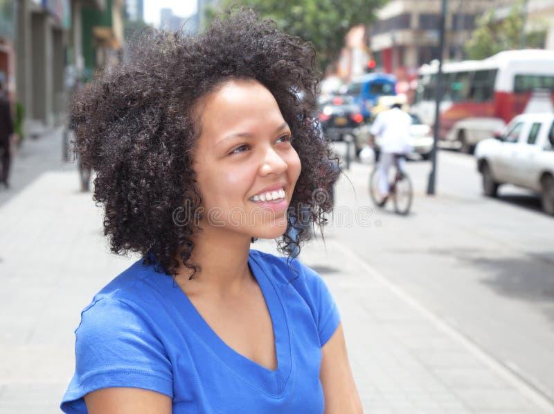 Träumen der Frau mit dem gelockten Haar in der Stadt stockbilder