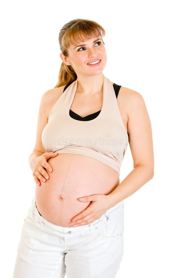 Träumen der schwangeren Frau, die ihren Bauch berührt stockbild
