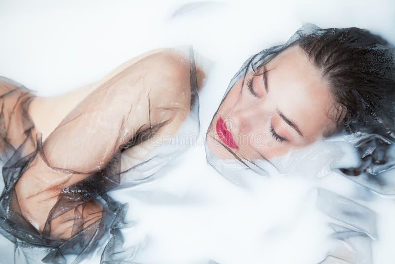 Träumen im milchigen Badschönheitsporträt mit schwarzem Tulle in der Milch stockbild