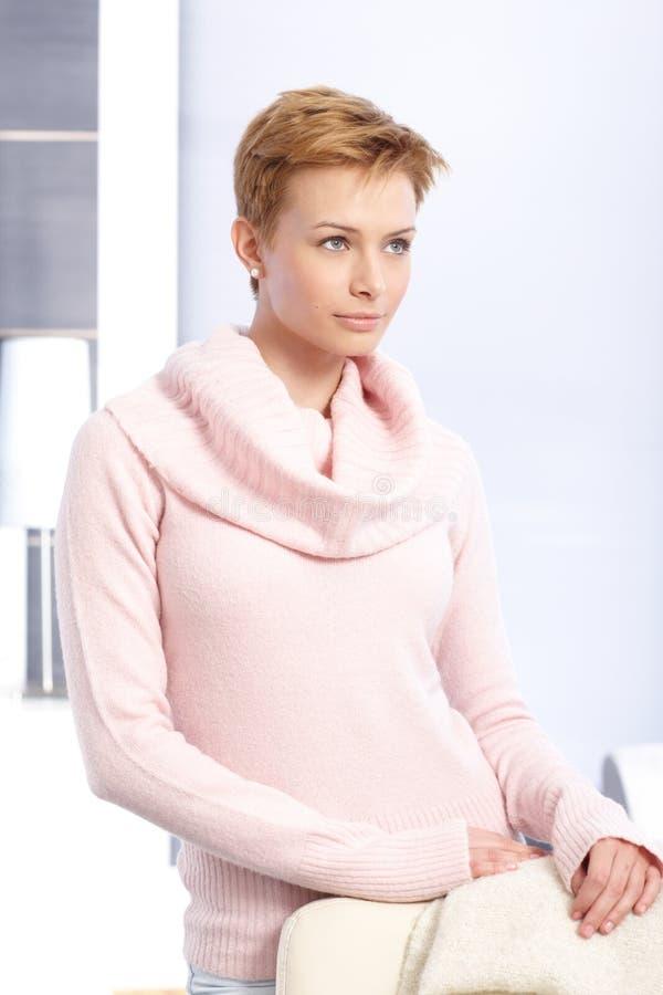 Träumende Frau, die im rosa Pullover steht lizenzfreie stockfotografie