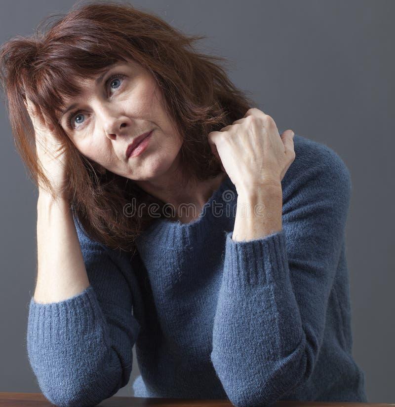 Träumende schöne Frau 50s, die nachdenklich schaut stockbilder
