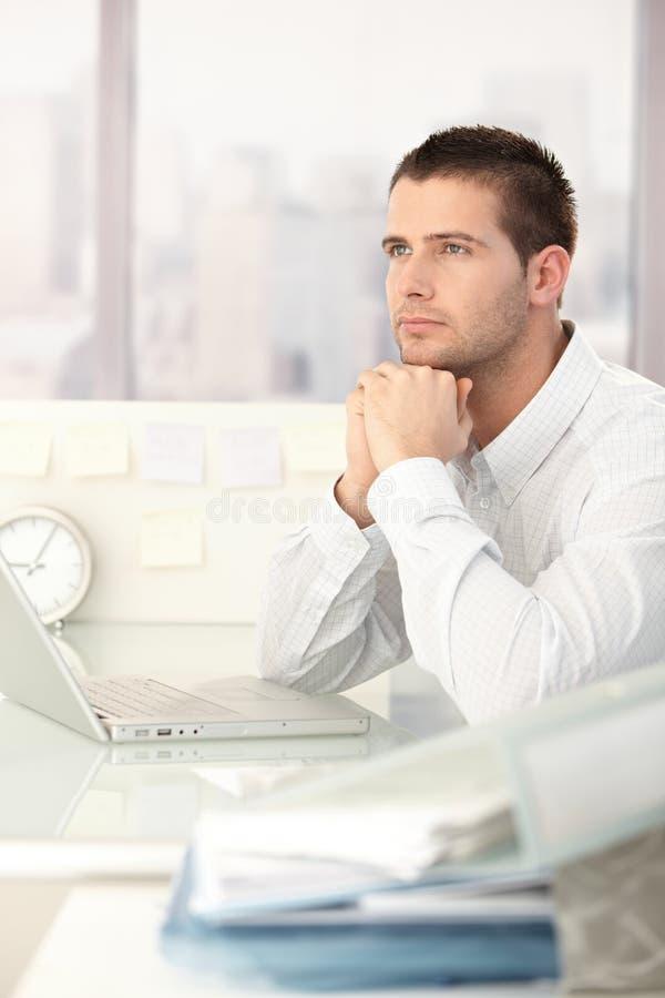 Träumender Geschäftsmann, der am Schreibtisch sitzt lizenzfreie stockfotografie