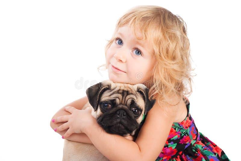 Träumendes Mädchen, das den Hund getrennt auf Weiß umarmt lizenzfreies stockbild