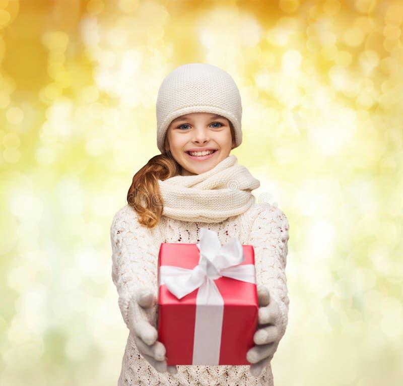 Träumendes Mädchen in der Winterkleidung mit Geschenkbox lizenzfreies stockfoto