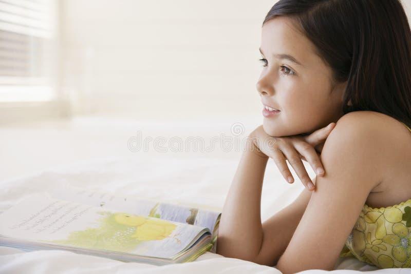 Träumendes Mädchen während Lesebuch stockfoto