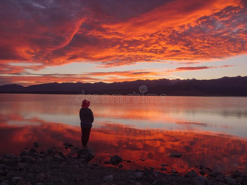 Träumer, Schattenbild der Frau stehend entlang dem See bei Sonnenuntergang, menschliche Stärke, Psychologiekonzept lizenzfreie stockfotos