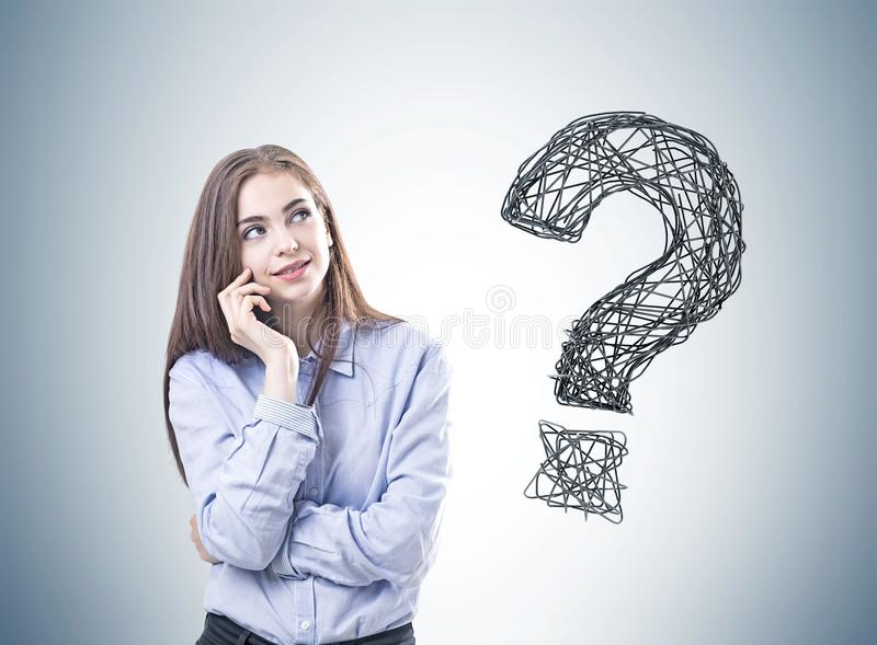 Träumerische junge Frau in einem blauen Hemd, Fragezeichen stockfotografie