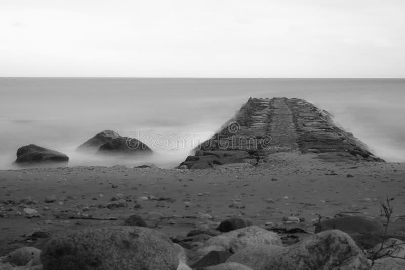 Träumerische Langbelichtung in Schwarzweiss, eines felsigen Strandes und der Anlegestelle, die auf den Horizont, Block-Insel, RI lizenzfreie stockfotos