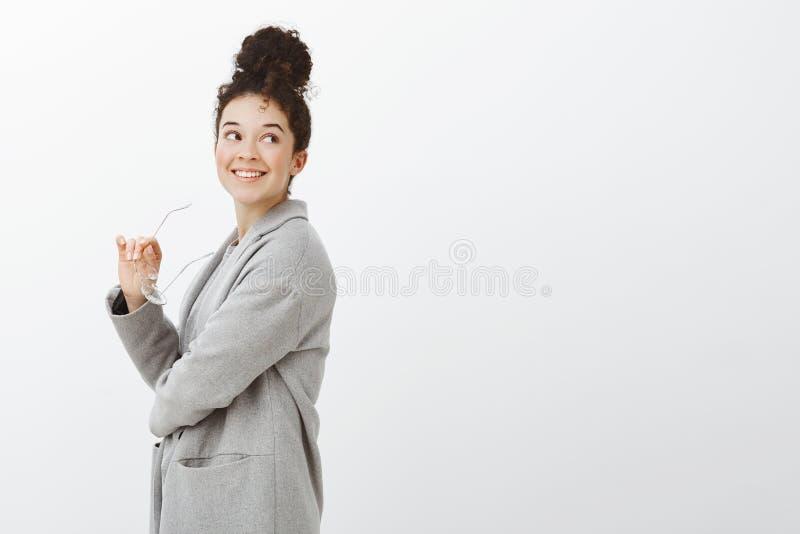 Träumerischer schöner städtischer europäischer weiblicher Unternehmer im modernen grauen Mantel, stehend im Profil und schauen re stockfoto