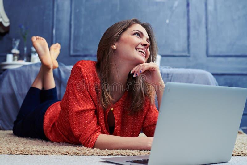 Träumerisches attraktives junges weibliches Lügen auf Boden mit einem silbernen lapt lizenzfreie stockbilder