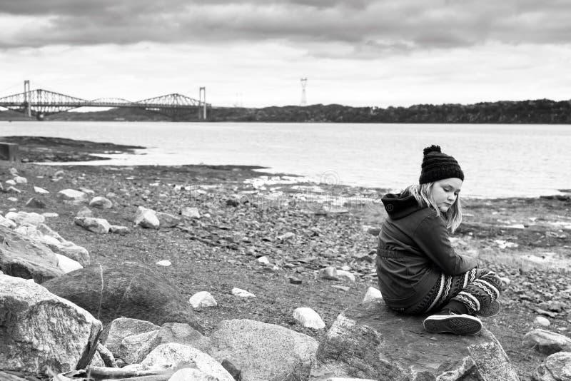 Träumerisches junges blondes Mädchen im Fall kleidet das Sitzen auf felsigem Strand lizenzfreies stockbild