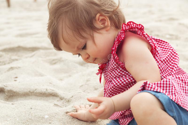 Träumerisches Kind Nettes dunkelhaariges Kinderkleines kleines Kinderbaby, das auf Hinterteilen sitzt und an mit Sand auf Strand  stockbild