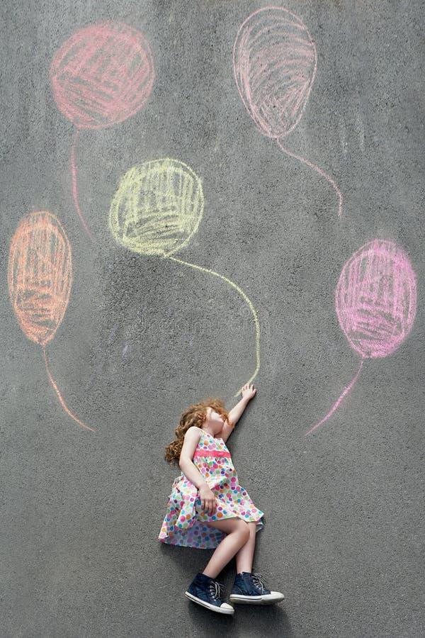 Träumerisches kleines Mädchen, das auf der Pflasterung mit gemalten Ballonen liegt lizenzfreie stockfotos