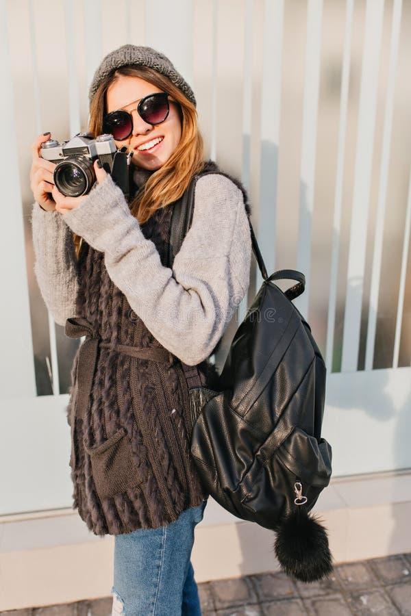 Träumerisches Mädchen in der Sonnenbrille mit der Kamera in der Hand, die oben mit bezauberndem Lächeln schaut Porträt im Freien  lizenzfreie stockfotos