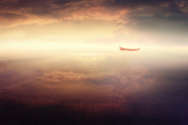Träumerisches rotes Boot am Strand stockfoto