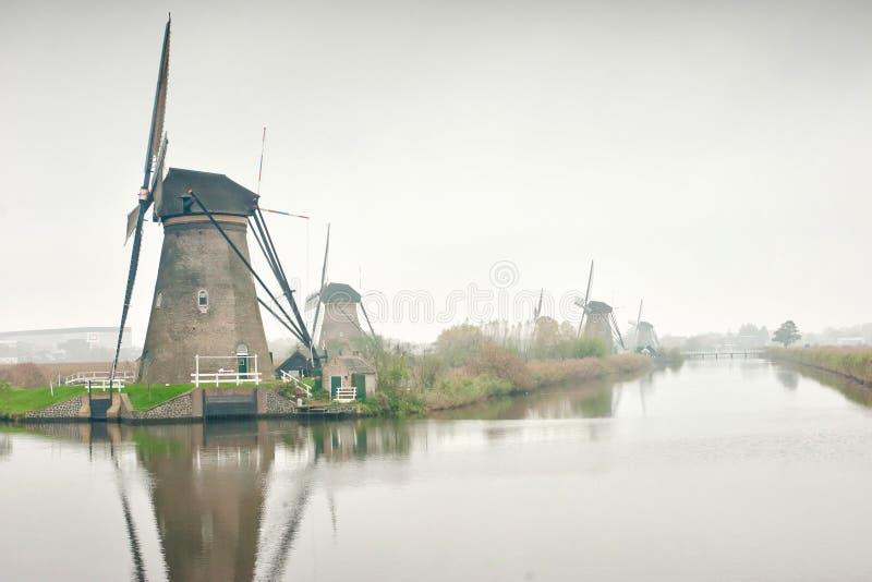 Träväderkvarnarna för berömd Nederländerna, UNESCOvärldsarv, Kinderdijk väderkvarnby i solnedgångljus av royaltyfria bilder