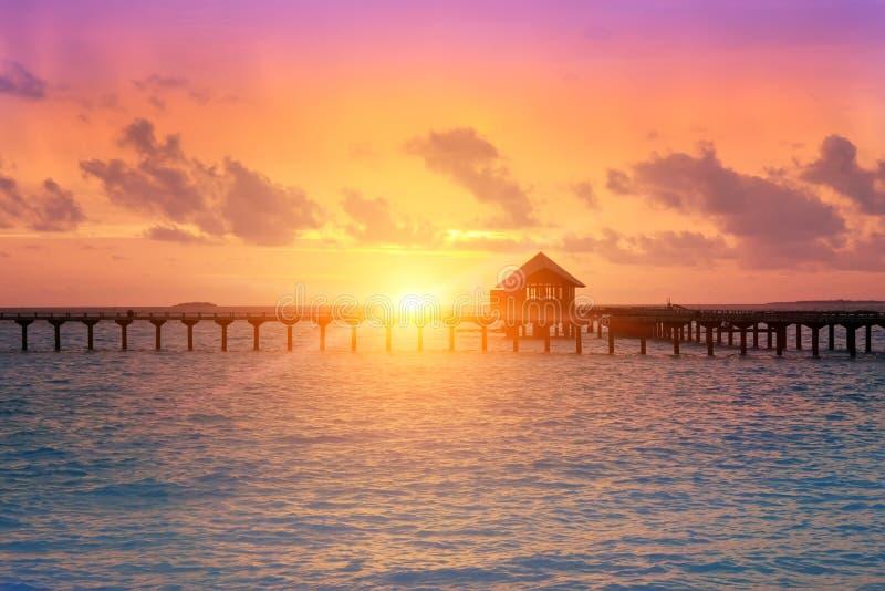 Träväg från ön till en koja över vatten på en solnedgång Maldiverna arkivfoto