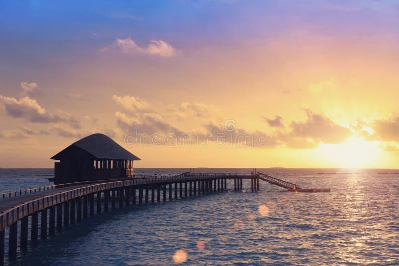 Trävägen över havet till den tropiska ön Solnedgång arkivbilder