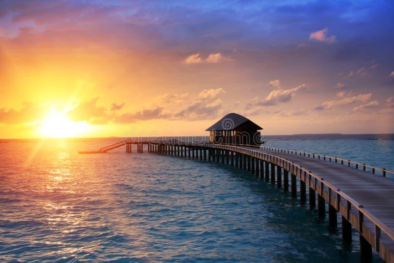 Trävägen över havet till den tropiska ön Solnedgång royaltyfria foton