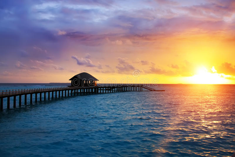 Trävägen över havet till den tropiska ön Solnedgång fotografering för bildbyråer