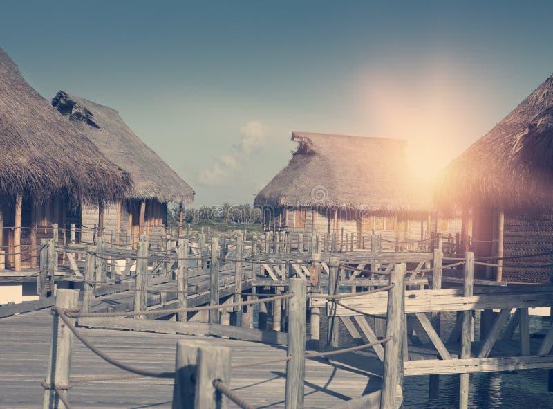 Trävägen över havet till traditionella logar på högar som tonar royaltyfri bild