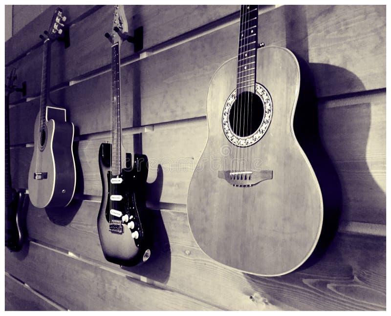 Trävägg av monterade gitarrer på skärm royaltyfri fotografi