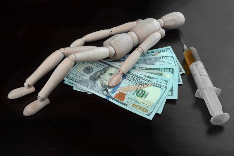 Trävuxen mänsklig statyett, dollarkassa och läkarundersökninginjektion royaltyfri foto