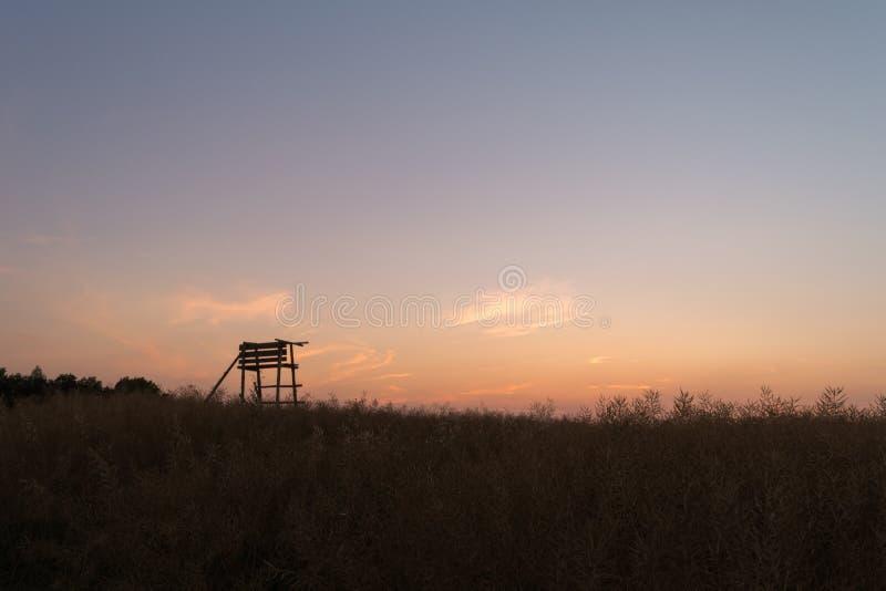 Träwatchtower som lokaliseras i ett fält under solnedgång arkivfoton