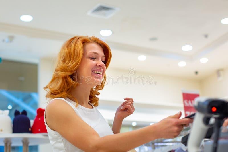 Trådlös betalning genom att använda smartphonen och NFC-teknologi close upp Den kvinnliga kunden som betalar med den smarta telef royaltyfri fotografi
