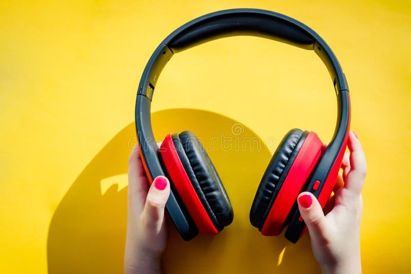 Trådlös hörlurar i kvinnlig hand på en gul bakgrund med annonsering av område som digital teknologi eller musik arkivfoto