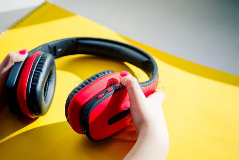 Trådlös hörlurar på livlig färgbakgrund Plan minsta stil Design och färger Stilfull modern hörlurar med royaltyfria foton