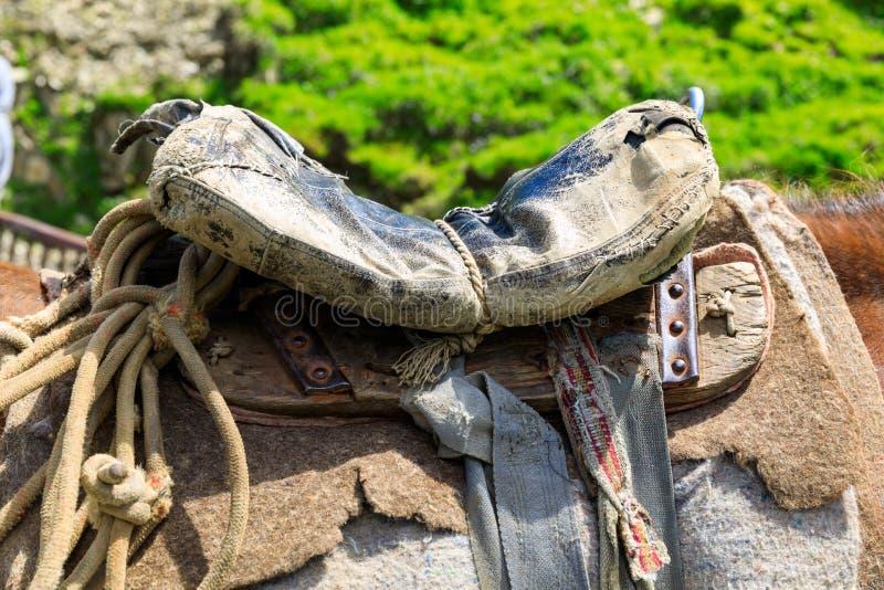 Trådsliten gammal sadel på en häst för herde` s, handgjord sadel av en bondaktig herde arkivbilder