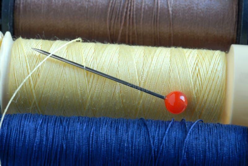 Trådspolar av olika färger med ett stift arkivfoton