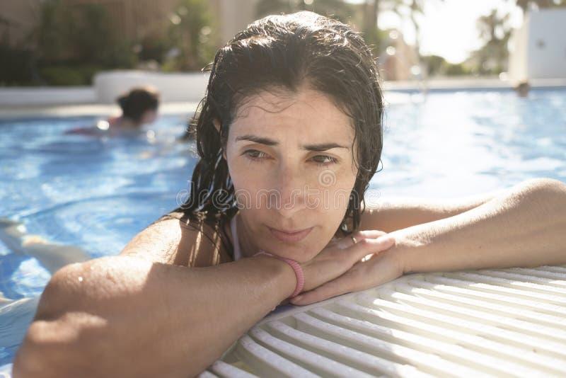 Tråkig eller tänkande kvinna i kant av simbassängen fotografering för bildbyråer