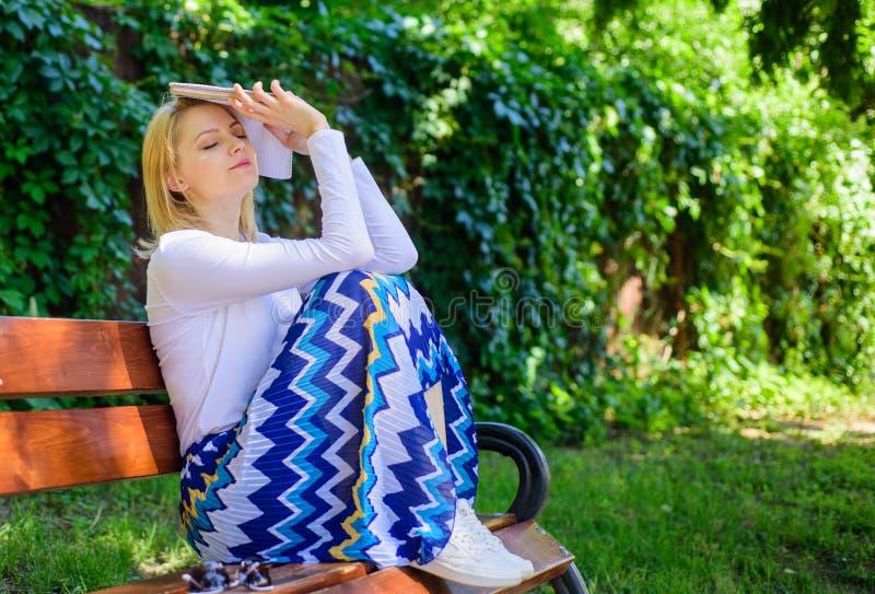 Tråkig litteratur Kvinnan tröttade det blonda tagandeavbrottet för framsidan som kopplar av i trädgårds- läsebok Damstudenten läs arkivfoto
