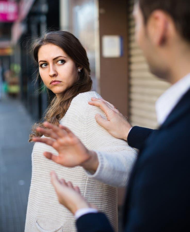Tråkig manlig person som tilltalar till kvinnlign på den fullsatta gatan arkivfoto