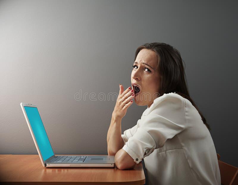 Tråkigt kvinnasammanträde med bärbara datorn royaltyfri bild
