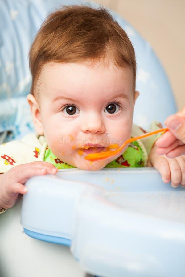 Très peu d'enfant mange des laits caillés nutritifs savoureux frais sur le highchair photo stock