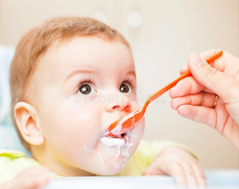 Très peu d'enfant mange des laits caillés nutritifs savoureux frais sur le highchair photos libres de droits