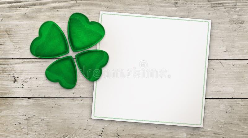 Trébol de cuatro hojas y tarjeta de felicitación en la madera fotos de archivo
