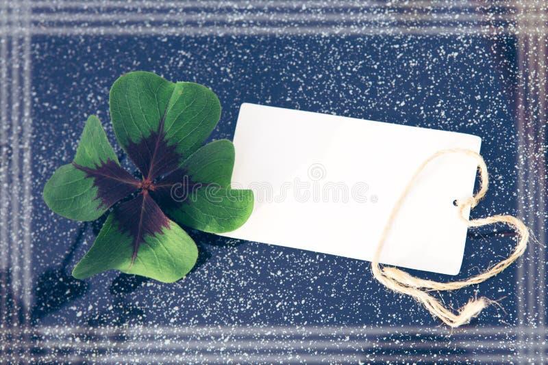 Trébol de cuatro hojas y tarjeta del día de fiesta Fondo del día de fiesta imagen de archivo libre de regalías