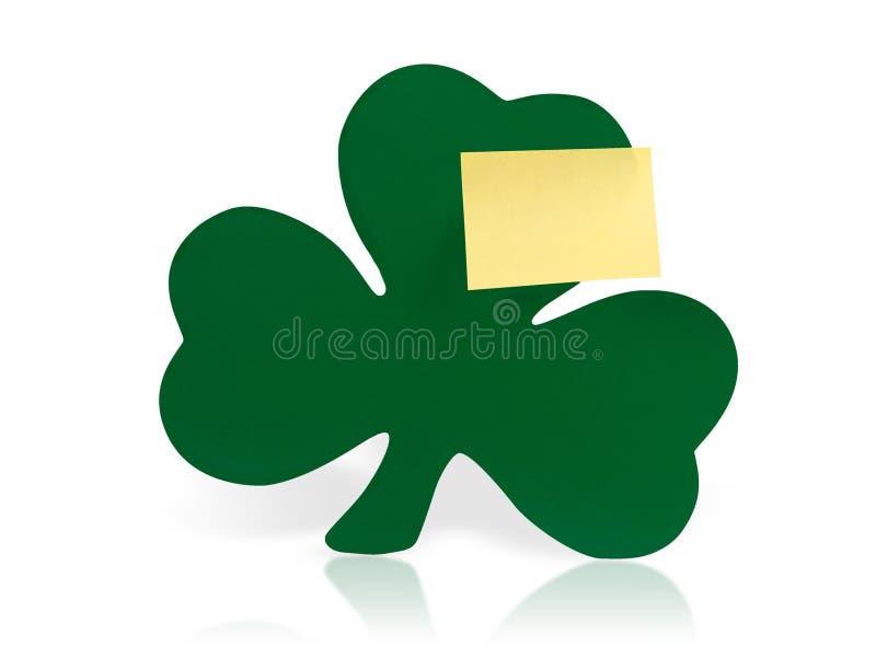 Trébol verde con la nota pegajosa amarilla fotografía de archivo libre de regalías
