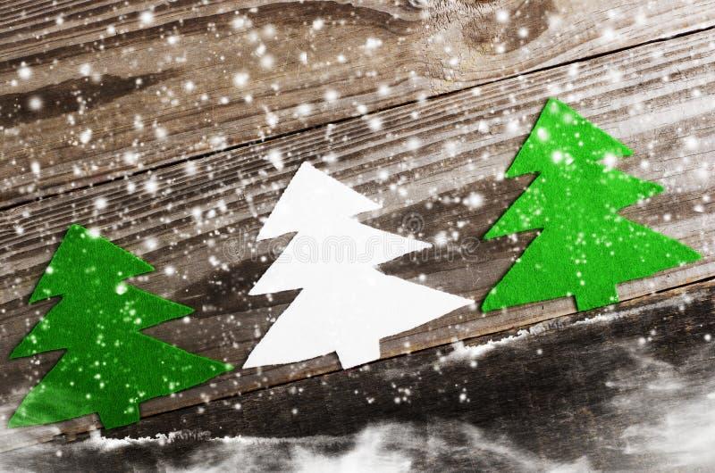Três árvores de Natal brancas e verde feito do feltro no fundo de madeira, nevado ofício foto de stock