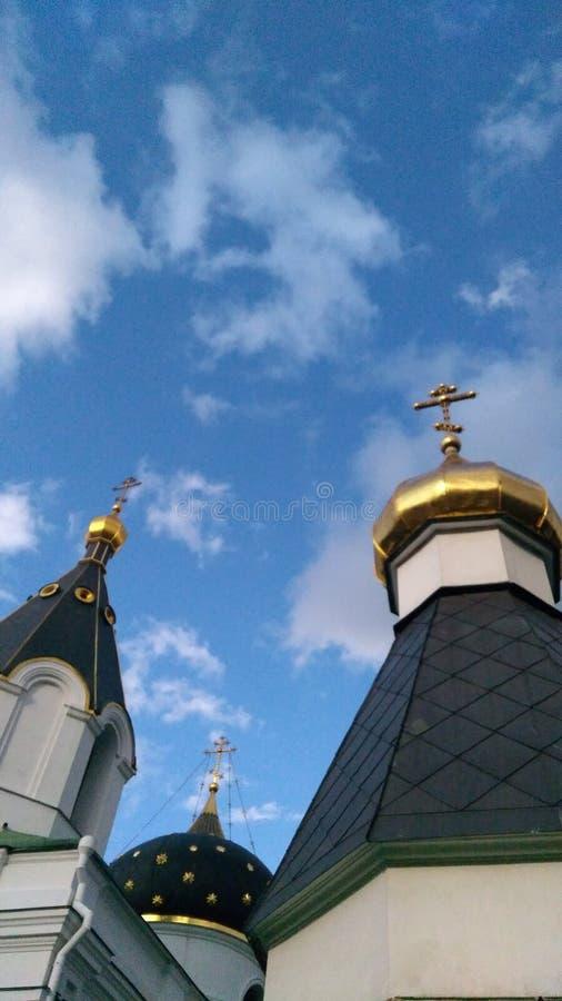 Três abóbadas com cruzes douradas da igreja ortodoxa do russo sob o céu azul com nuvens foto de stock royalty free