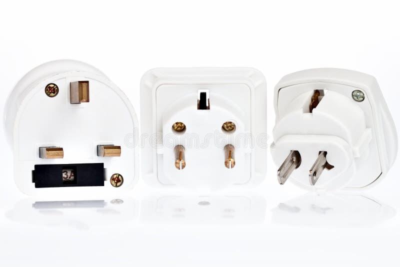 Três adaptadores elétricos em um fundo branco foto de stock